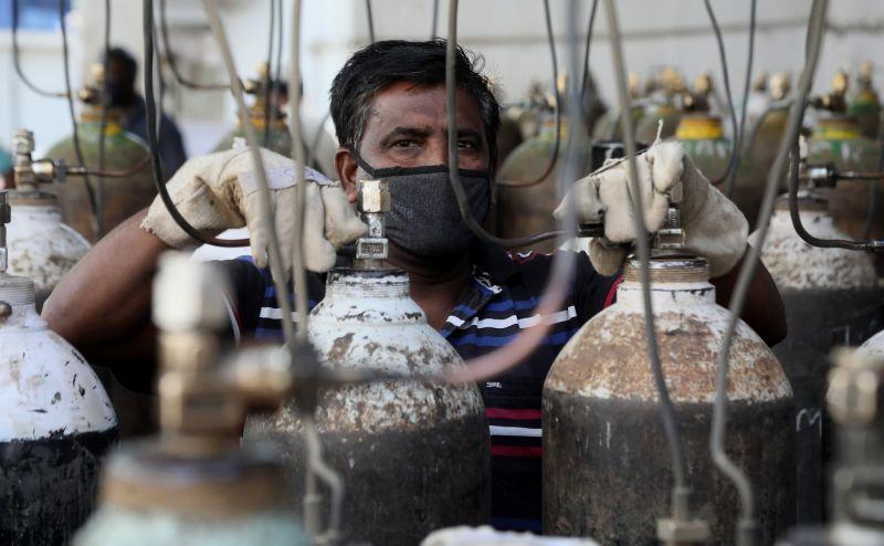 Worker refilling oxygen tanks, India