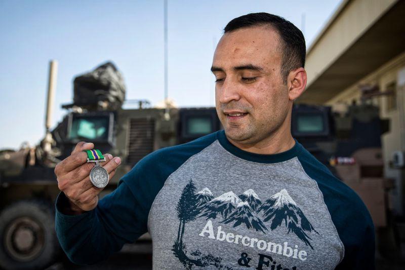 Interpreter Sadruddin Stori displays Australian Operational Service Medal - Civilian